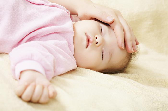 赤ちゃんのおでこを撫でる