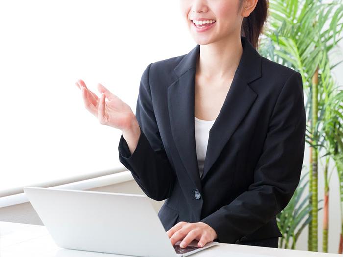 パソコンをもって説明する女性